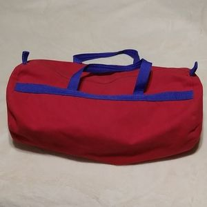 Red canvas duffle bag with blue straps